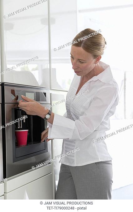 Mature woman preparing coffee in modern kitchen
