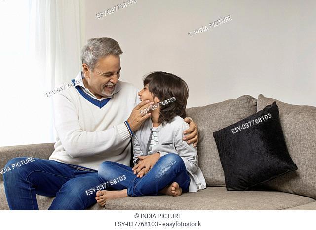 Smiling grandfather pampering grandson sitting on sofa