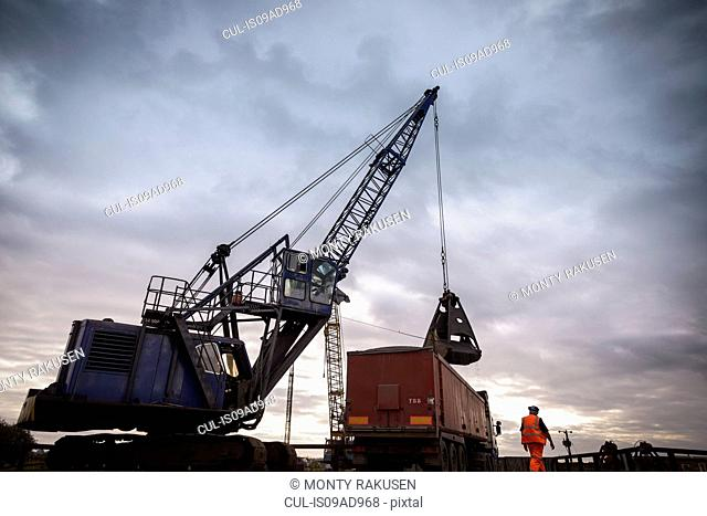Low angle view of crane loading truck under dramatic sky