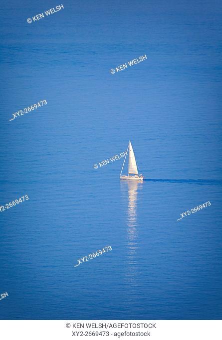 Lone yacht sailing off Riviera dei Fiori, of the Coast of Flowers, Imperia Province, Liguria, Italy