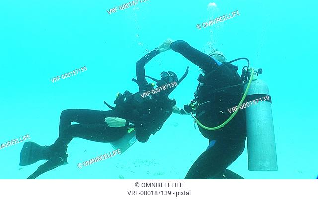 Older male and female scuba divers partner dancing underwater