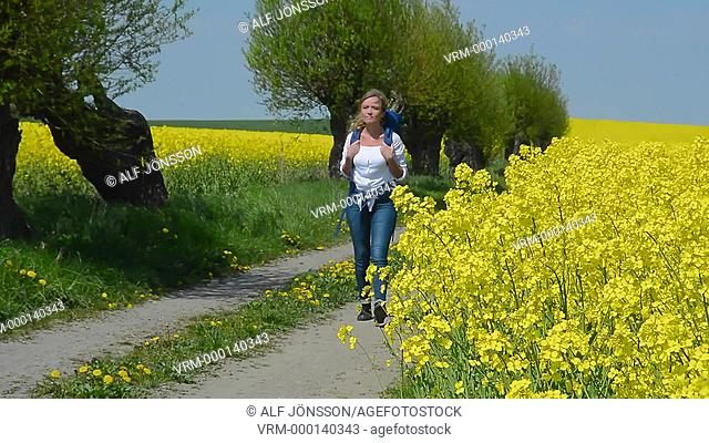 Young woman walks on a tiny road among willow tree and rape
