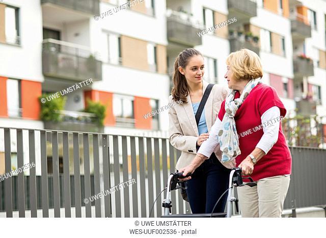 Granddaughter assisting her grandmother walking with wheeled walker