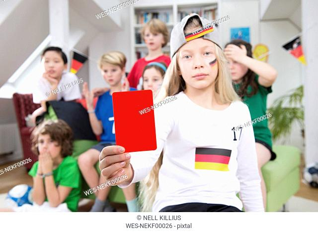 Girl showing red card in front of friends, watching football world cup