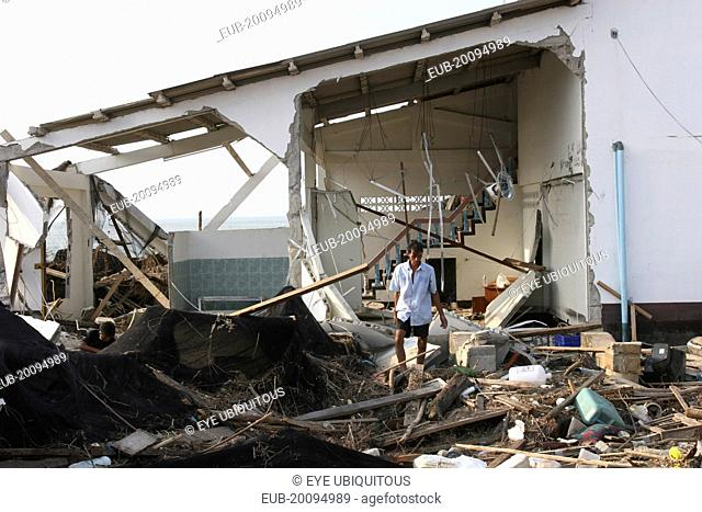 Tsunami. A man stands outside of what is left of his house and tries to salvage what he can from the damage caused by the tsunami