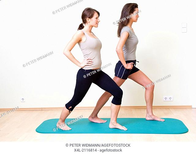 Two young women doing gymnastics on a mat, lunge (model-released)