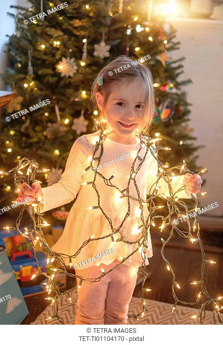 Little girl (4-5) wrapped with christmas lights in living room