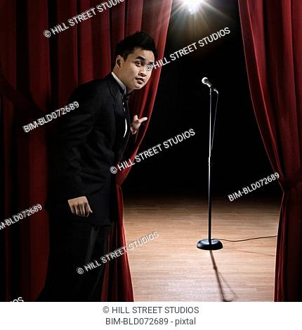 Asian man in tuxedo standing backstage