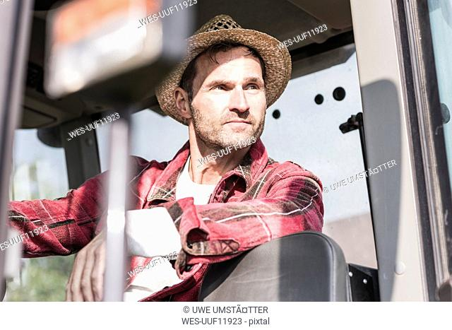 Portrait of confident farmer on tractor