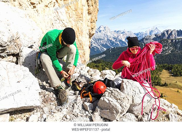 Italy, Cortina d'Ampezzo, couple getting ready for climbing in the Dolomites mountains