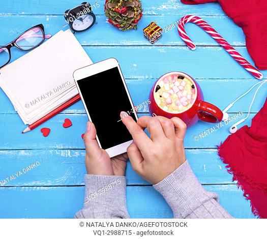 smartphone with an empty black screen in female hands, next to a cup of coffee with marshmallows