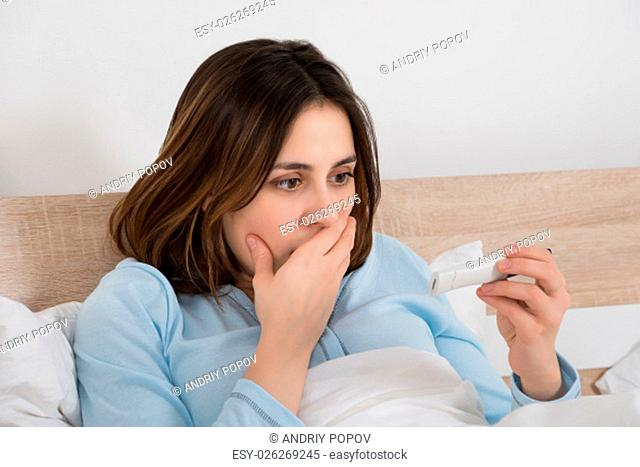 Worried Young Woman Checking Pregnancy Test On Bed
