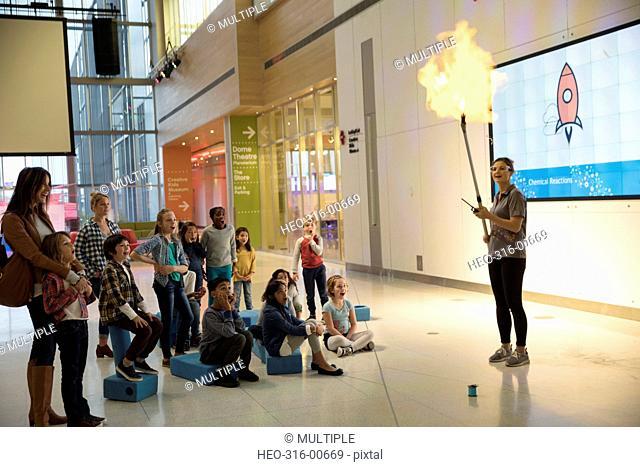 Children watching scientist conducting rocket fire demonstration in center center