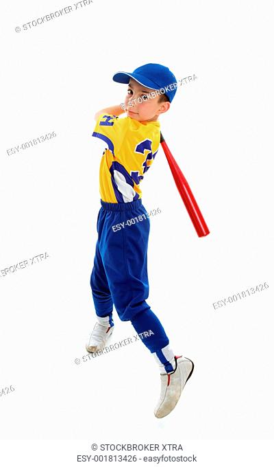 A young child wearing a baseball or softball uniform swinging a bat on a white background