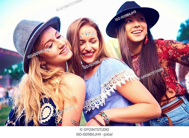 Three young female friends in fedoras dancing at festival