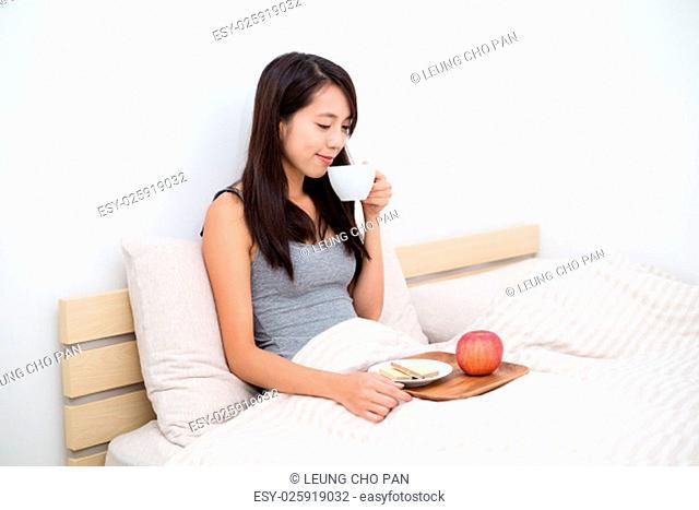 Woman having breakfast on bed