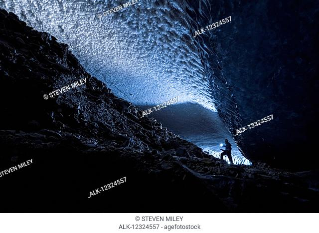 A man illuminates a dark tunnel beneath the ice of Canwell Glacier with a flashlight, Interior Alaska, USA
