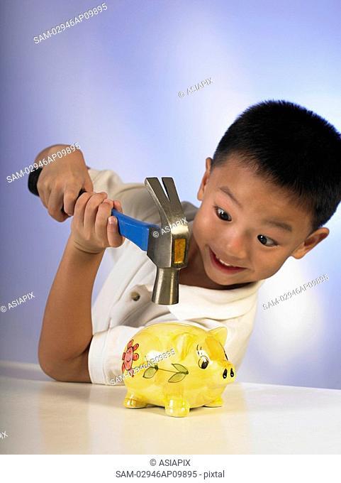 boy hitting a piggy bank with a hammer