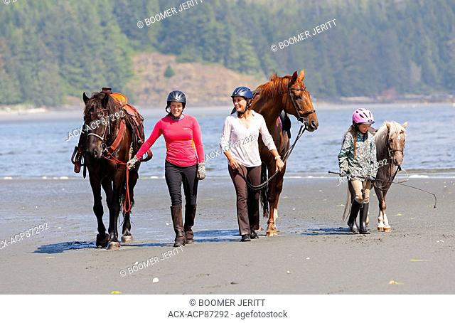 Friends walk their horses at low tide along Stories Beach near Port Hardy