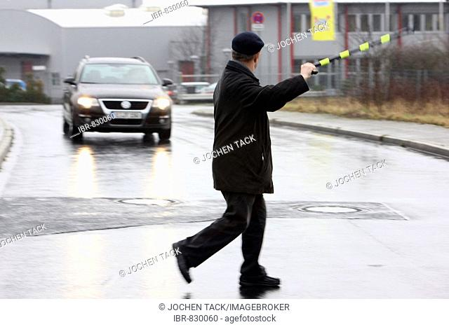 Old man trying to cross a street using his walking stick to slow down an oncoming car, Mettmann, North Rhine-Westphalia, Germany, Europe