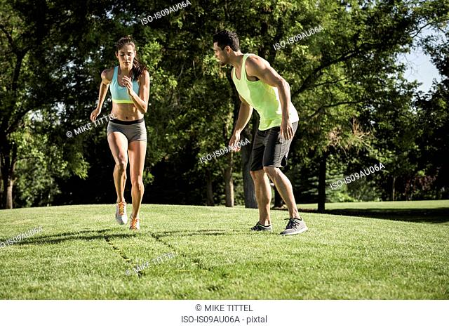 Young woman and teammate training with agility ladder in park