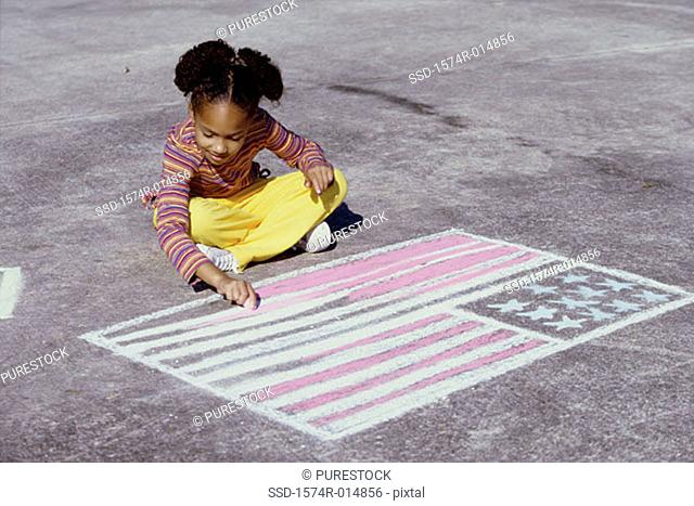 High angle view of a girl drawing an American flag on the ground with chalk