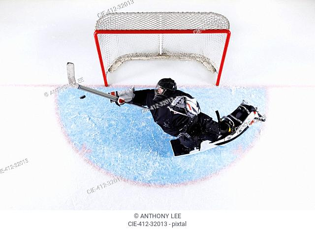 Overhead view hockey goalie reaching to block puck at goal net