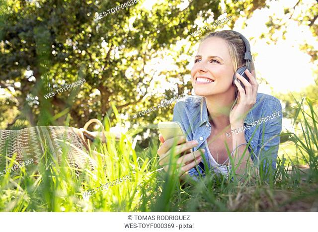 Smiling woman lying on meadow listening to music from smartphone