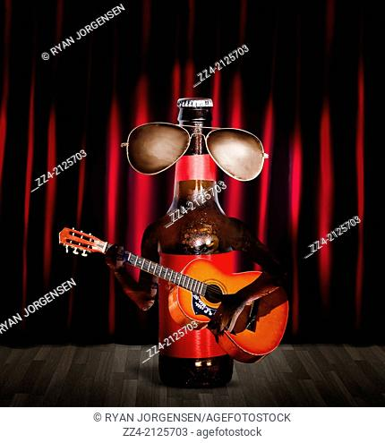 Unopened beer bottle music performer wearing cool aviator sunglasses playing acoustic guitar on stage in front of bright lights and red curtains
