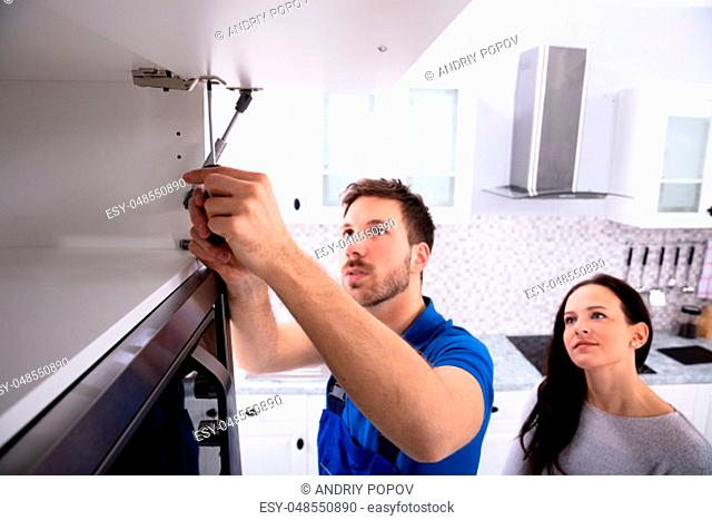 Woman Looking At Male Handyman Installing Cabinet Door In The Kitchen