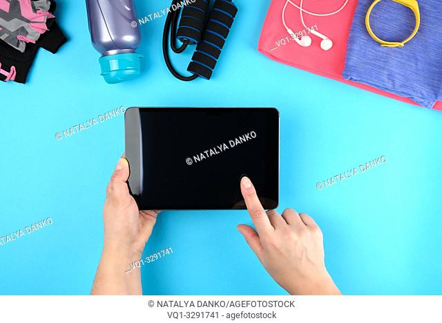 female hands holding an electronic tablet with a blank black screen, next to it is fitness clothes, blue background, top view