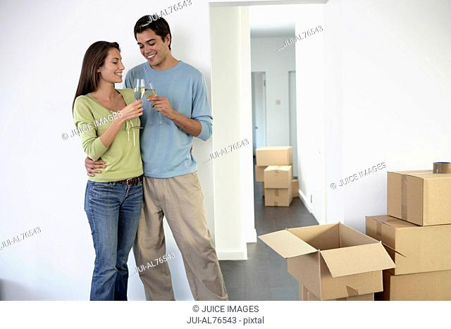Portrait of a young couple toasting each other as they move into a new house