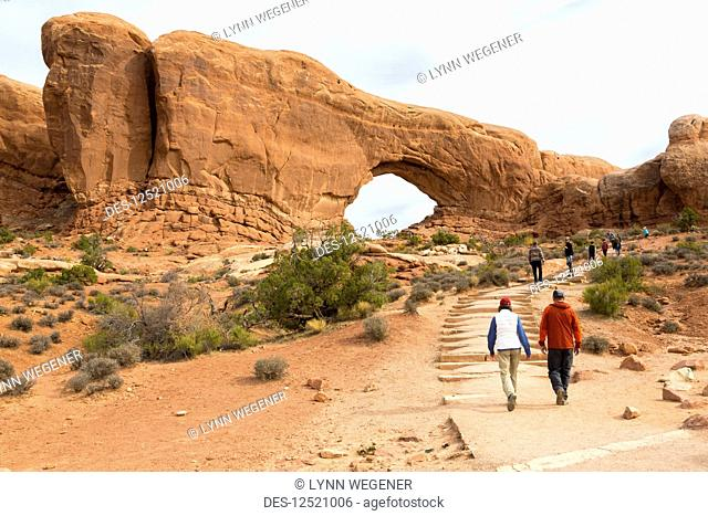 Two hikers approaching Window Arch, Arches National Park, Utah, United States of America