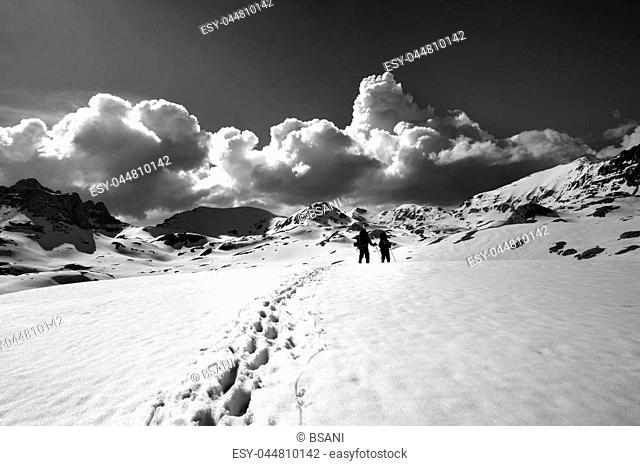 Black and white view on snow plateau with hikers. Turkey, Central Taurus Mountains, Aladaglar (Anti-Taurus), plateau Edigel (Yedi Goller)