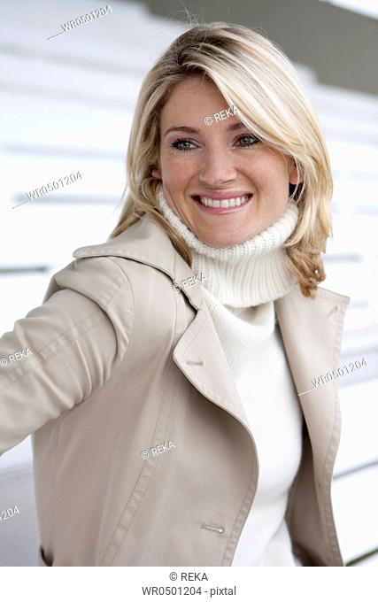 Smiling blond woman wearing coat