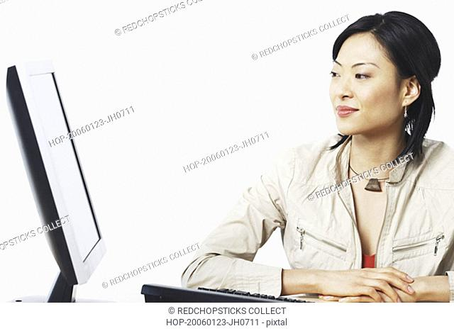 Close-up of a businesswoman smiling near a computer