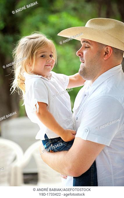 Father with cowboy hat carrying his cute four years old daughter