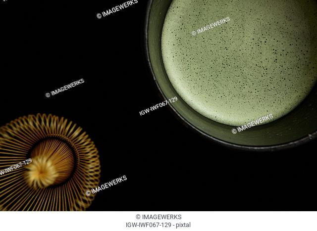 Matcha Japanese powdered green tea and tea whisk against black background, close-up