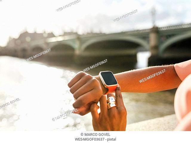 UK, London, close-up of woman using her smartwatch near Westminster Bridge