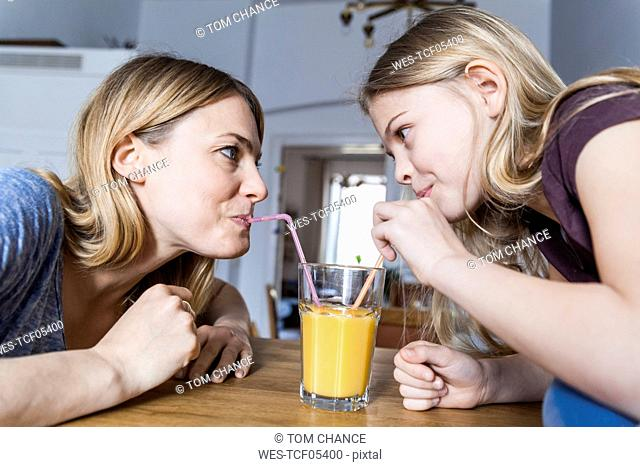 Mother and daughter sharing an orange juice in kitchen