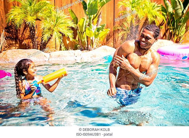 Father and daughter playing with water pistol in swimming pool
