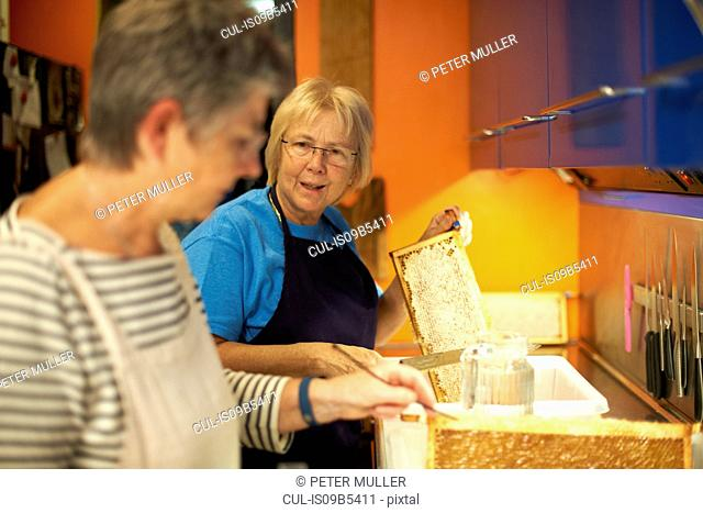 Two senior female beekeepers scraping honeycombs in kitchen