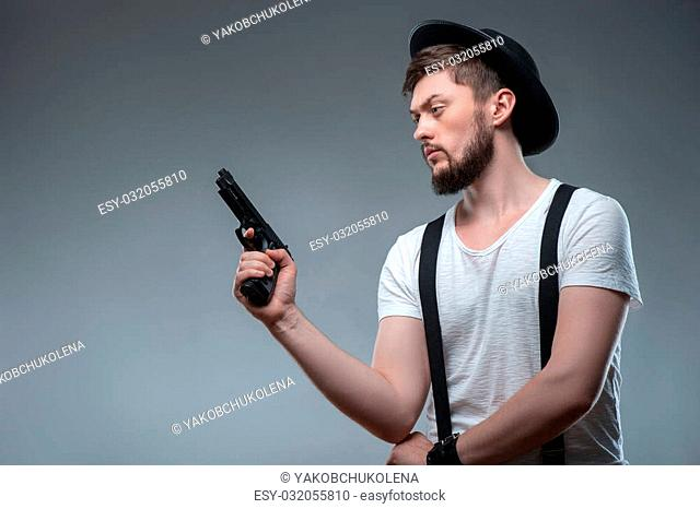 Handsome guy threatens to kill someone with gun. He directs it aside. He is looking at gun with seriousness and confidence