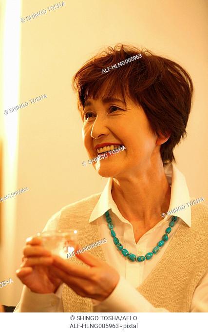 Fashionable Japanese senior woman drinking sake