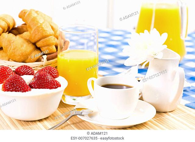continental breakfast: coffee, strawberry and cream, croissant and juice