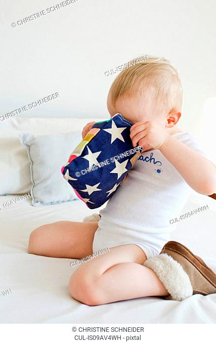 Female toddler peering into pencil case on bed