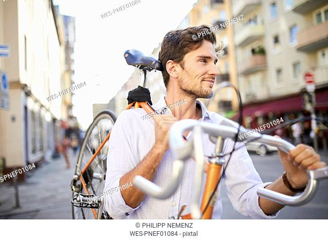Content young man carrying his racing cycle on shoulder in the city