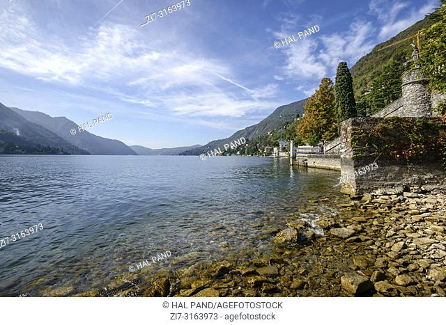 landscape of green lake coast of Como lake from stone beach, shot toward south in bright fall light at Urio, Como, Italy