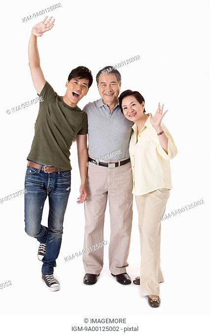 Family standing and smiling at the camera happily