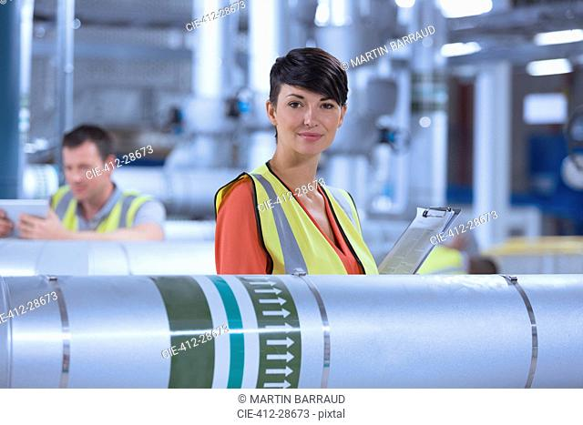 Portrait confident female worker with clipboard in factory